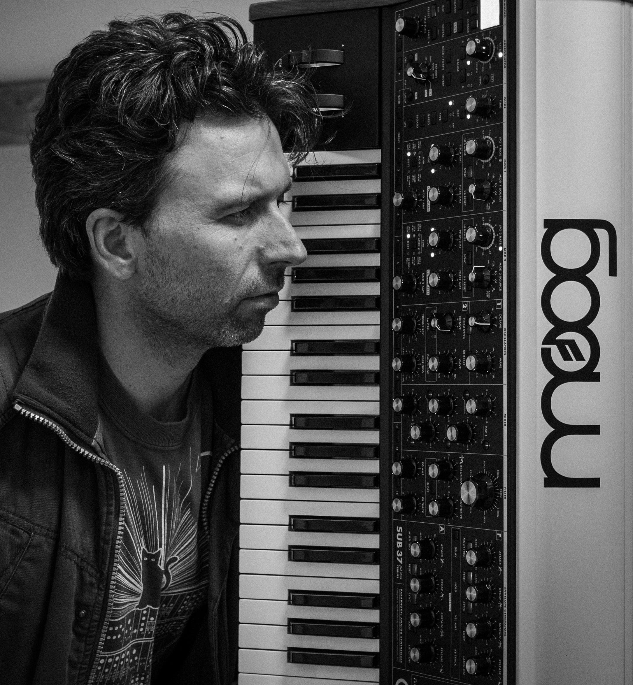 Robin Bigwood staring at knobs of a Moog SUB37 synthesizer